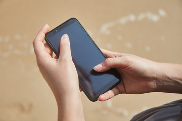 Mobile phone in female hand on the background of the beach and ocean