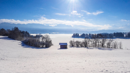Winter landscape with lake and Alps