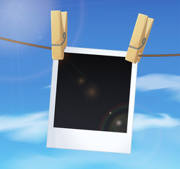 Photoframe on blue sky background, white clouds and clothes pins