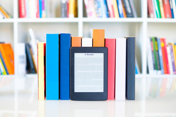 Ebook reader and paper books on bookshelf background.
