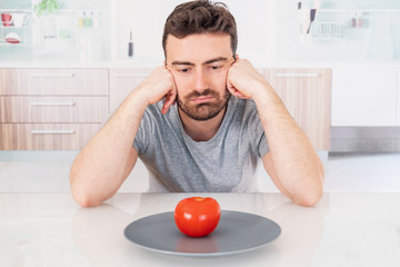 Worried man hungry and starved with salad