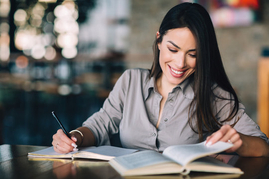 Young woman holding book and pencil for taking notes
