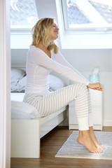 Junge Frau im Schlafanzug sitzt auf einer Bettkante und streckt sich