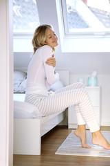 Junge blonde Frau sitzt lachend auf einer Bettkante