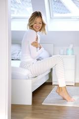 Junge Frau sitzt lächelnd auf ihrem Bett