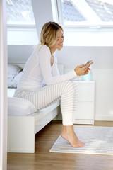 Frau mit smartphone sitzt auf ihrem Bett und lacht
