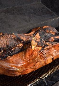 Ganzes, gegrilltes Schwein auf einem Grill im Rauch mit Salat und Orangen