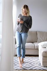 Junge Frau mit einer Tasse in den Händen lacht