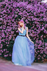 a pink-haired girl stands in a luxurious, blue dress. Background fantastic garden lilac.