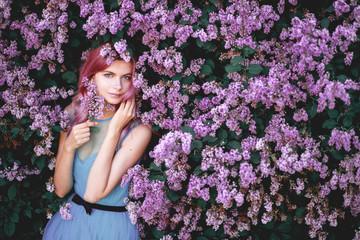 Fine art portrait of girl in dress in lilac garden