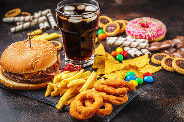 Fototapeta Junk food concept. Unhealthy food background. Fast food and sugar. Burger, sweets, chips, chocolate, donuts, soda. obraz