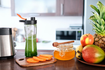 Green smoothie in  bottle on the home kitchen. The concept of healthy eating.