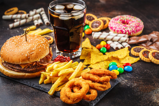 Junk food concept. Unhealthy food background. Fast food and sugar. Burger, sweets, chips, chocolate, donuts, soda.