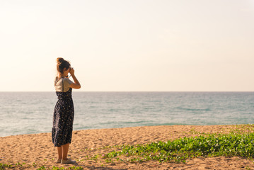 young woman stands on the beach and use mobile phone takes a photo with beautiful amazing sea sunset of orange red colors