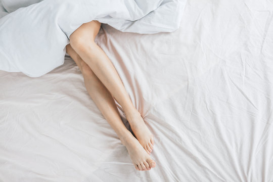 sexy legs in the bed .top view photo. copy space . woman is taking care of her body