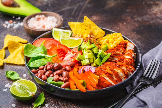 Mexican chicken burrito bowl with rice, beans, tomato, avocado,corn and spinach. Mexican cuisine food concept.