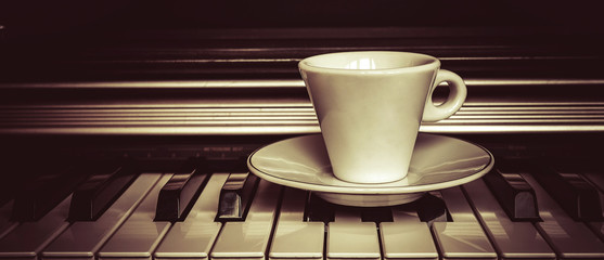 Cup of coffee on piano keys with copy space, concept of coffee break musical pause