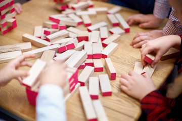 The child plays in a tower of wooden bars. Floors of wooden pieces. The child takes out the bars from the floors of the tower. Board game.