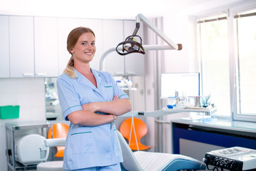 Portrait of cute female dentist standing In clinic.