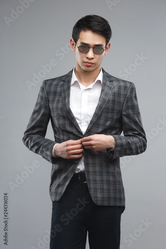 ca39efe38e37 Young asian man in business suit and sunglasses isolated on gray background.