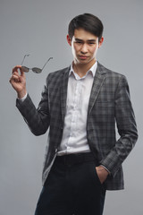 Young asian man in business suit with sunglasses in hand isolated on gray background.