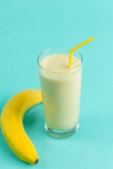 Spoed Foto op Canvas morning breakfast, vitamins, wellbeing, milkshake with a banana on the blue background. weight lose