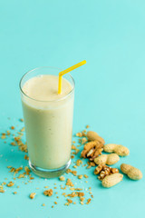 Spoed Foto op Canvas a glass of vanilla milkshake isolated on blue background. isolated blue background. diet concept