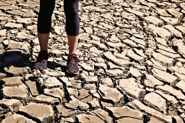 A women standing on a dry cracked river bed. Drought concept image.