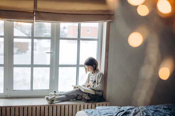 cute little girl with a book. side view photo. pleasant adorable girl is concentrated on reading her favourite book