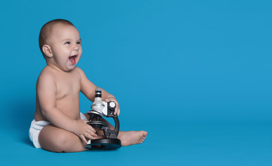 Adorable baby boy with microscope, copy space
