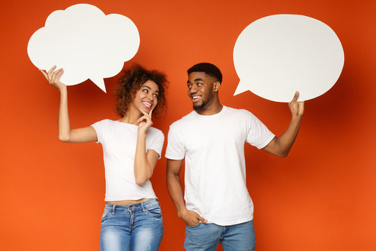 Young black couple holding speech bubbles on orange background