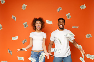 Young black couple standing under money banknotes shower