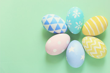 Pastel and colorful easter eggs with copy space on green background..
