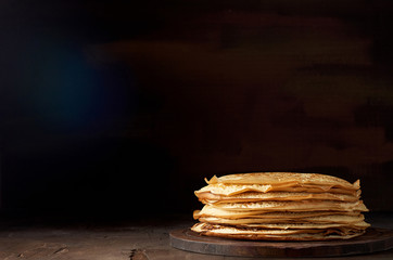 Stack of russian pancake blini on a wooden background