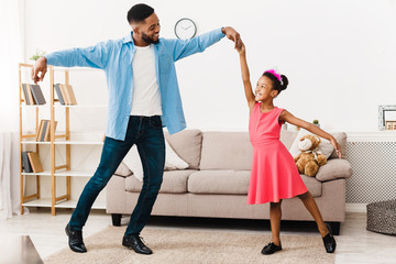 African-american father dancing with his little daughter