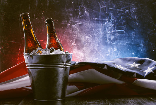 two bottles of beer in an ice bucket with the American flag lying nearby. Independence Day celebration concept