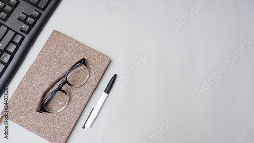 Wall mural notebook with keyboard and glasses on gray background business concept desk table