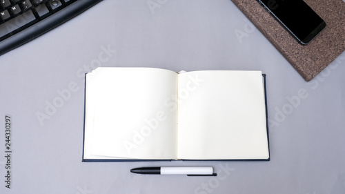 Wall mural notebook with smart phone and pen on gray background business concept desk table