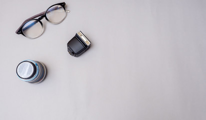 Canvas Print - lens and glasses with flash camera on gray background business concept desk table
