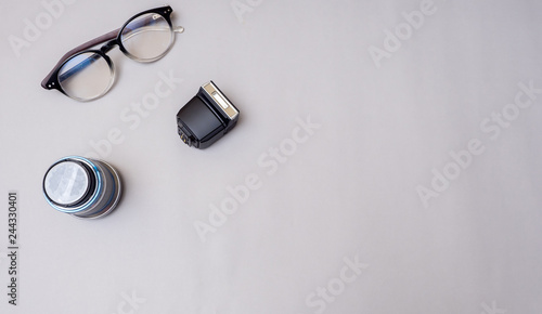 Wall mural lens and glasses with flash camera on gray background business concept desk table