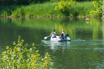 Zwei Mädchen paddeln in einem Schlauchboot auf einem See