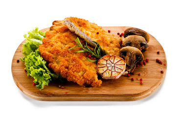 Fried pork chop with champignon on cutting board on white background