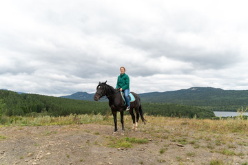 The girl sits on a horse. Beautiful nature around, there is a small lake.