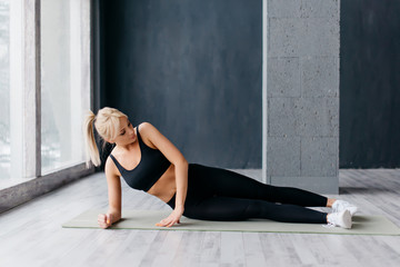 young sports woman exercising on mat in fitness studio
