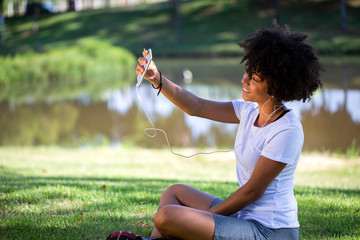 Closeup portrait of smiling young attractive African American woman holding smartphone, taking selfie photo and standing in park with blurred plants in background - Imagem