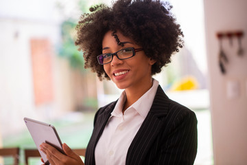 Close up portrait black business woman employee in glasses working in office with tablet looking at camera