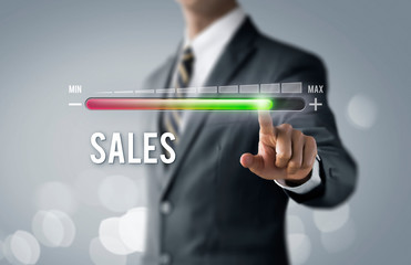 Sales growth, increase sales or business growth concept. Businessman is pulling up progress bar with the word SALES on bright tone background.