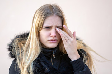 Woman with eye problems outside in winter