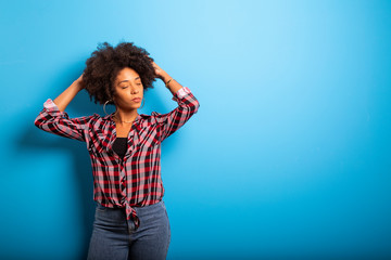 Portrait of cool young black woman laughing against blue wall - Imagem