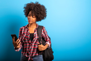 Closeup portrait of smiling young attractive African brazilian woman holding smartphone on the blue background